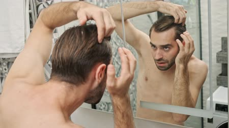 ひげを剃っていない : Back view of displeased handsome young bearded shirtless man touching his hair while looking at the mirror in the bathroom 動画素材