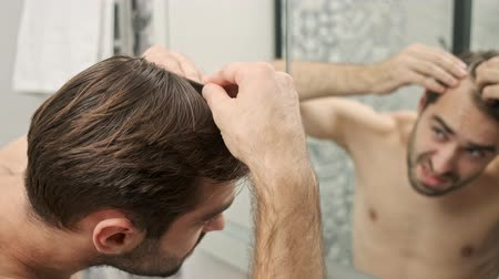 ból pleców : Close up view of unhappy handsome young bearded shirtless man having some problems with his hair while looking at the mirror in the bathroom