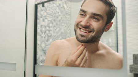 ひげを剃っていない : Reflection of cheerful handsome young bearded shirtless man touching his beard and hair while looking attentively at the mirror in the bathroom 動画素材