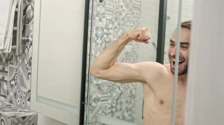 skóra : Reflection of cheerful handsome young bearded shirtless man showing his biceps and shouting while looking at the mirror in the bathroom