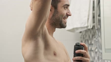 dezodorant : Side view of pleased handsome young bearded shirtless man smiling and applying deodorant on armpit while looking at the mirror in the bathroom Wideo