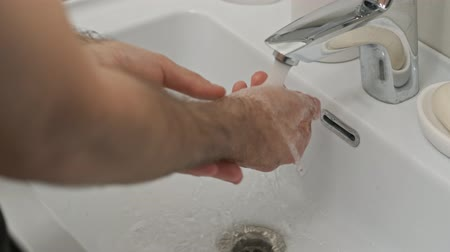 молодой взрослый человек : Cropped view of man washing his hands in sink indoors at the bathroom