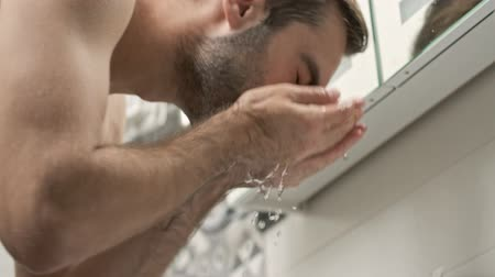 lavatório : Bottom view of calm handsome young bearded shirtless man washing his face in sink and looking at the mirror in the bathroom Vídeos