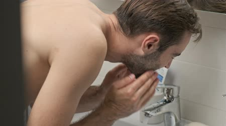 lavatório : Side view of smiling handsome young bearded shirtless man washing his face while standing at the bathroom sink
