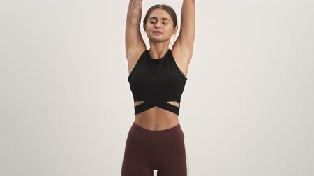 cardio workout : Sporty woman wearing tracksuit staying in a calm pose raised arms overhead isolated over white wall
