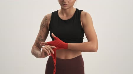 argomento : Cropped view of young sporty woman wearing tracksuit putting on boxing hand wraps isolated over white wall