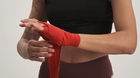 argomento : Close up view of strong sporty woman wearing tracksuit putting on boxing hand wraps isolated over white wall Filmati Stock