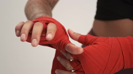 téma : Close up view of young woman wearing tracksuit putting on red boxing hand wraps isolated over white wall