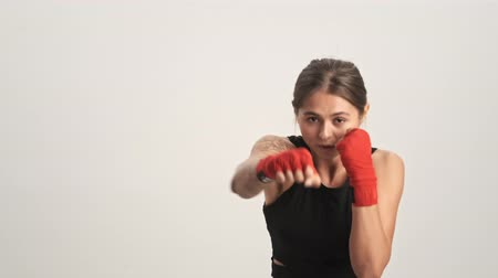 legginsy : Beautiful strong woman wearing tracksuit and boxing in red hand wraps fighting to the camera isolated over white wall