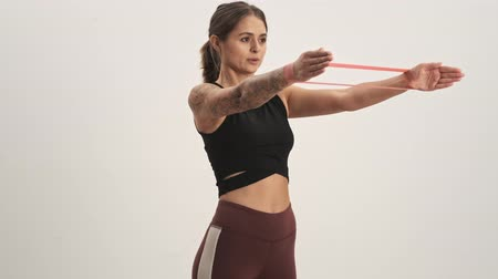 cardio workout : Strong young woman wearing tracksuit making exercises with her hands only using expander fitness tape isolated over white wall