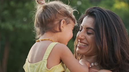fondness : Laughing indian woman having fun with her cheerful child girl outdoors