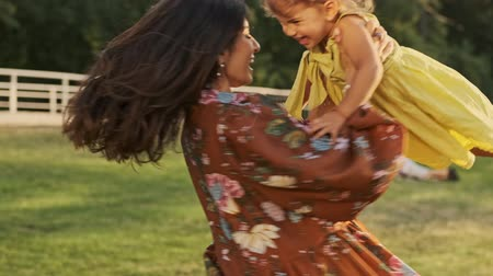 whirling : Pleased indian woman having fun with her happy child girl and whirling her in park outdoors