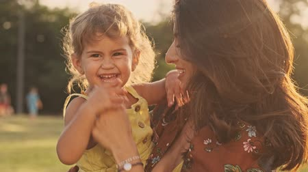 fondness : Pleased indian woman enjoys the moment with her happy child girl and whirling her in park outdoors Stock Footage