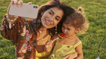 candy : Smiling indian woman making selfie on smartphone with her pleased child girl which eating lollipop in park outdoors