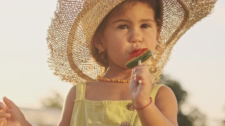 diyabet : Pleased pretty child in straw hat eating lollipop and enjoys in park outdoors