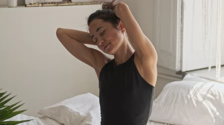oneself : Pleased pretty asian woman wakes up and stretch oneself with closed eyes while sitting on bed at home Stock Footage