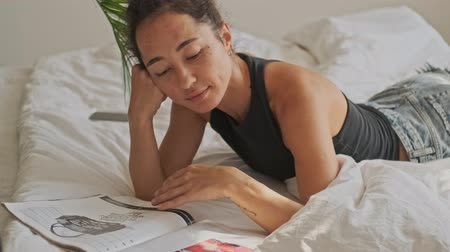 tuvalet : Carefree pretty asian woman reading magazine and relax while lying on bed at home