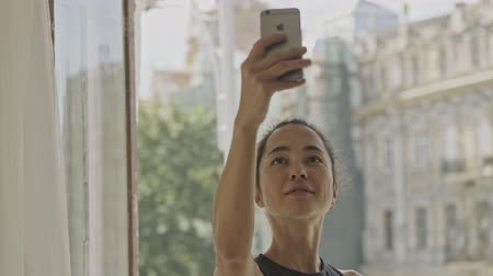 satisfait : Pleased pretty asian woman standing near the window and making selfie on smartphone at home