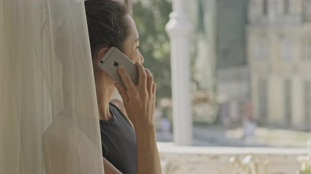 záchod : Side view of happy pretty asian woman standing near the window and talking by smartphone at home Dostupné videozáznamy