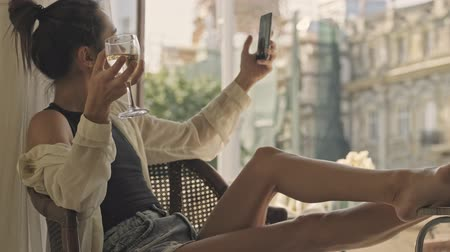 záchod : Side view of pleased carefree pretty asian woman making selfie on smartphone and drinking wine while sitting on armchair near the window at home Dostupné videozáznamy