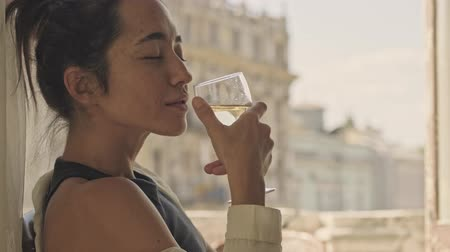закрытыми глазами : Side view of pleased carefree pretty asian woman drinking wine and enjoys this moment with closed eyes while sitting on armchair near the window at home