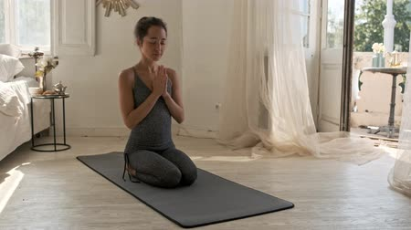 закрытыми глазами : Carefree asian woman meditation with closed eyes and pray gesture on mat at home Стоковые видеозаписи