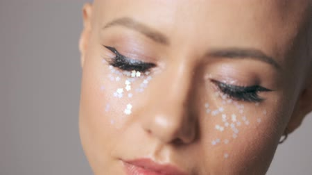head over : Close up view of young hairless woman with fashion eye makeup looking to the side isolated over gray wall Stock Footage