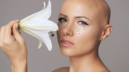 head over : Beautiful young hairless woman with fashion eye makeup posing with white lily bud while looking to the camera isolated over gray wall