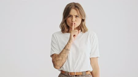 taboo : Beautiful young woman wearing white basic t-shirt holds finger on lips making silence gesture isolated over white background