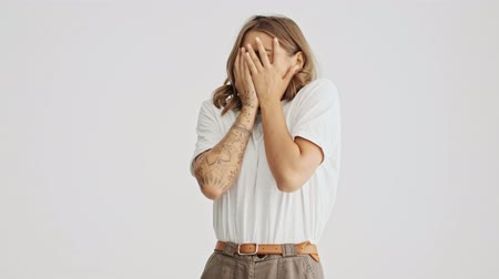 скрывать : Scared young woman wearing basic t-shirt hiding her face with her arms looking through fingers isolated over white background
