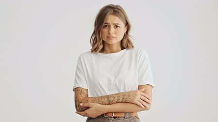 sentiment : Sad beautiful young woman wearing basic t-shirt standing with arms folded isolated over white background Stock Footage