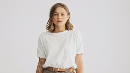 ruch : Pretty young woman wearing a basic white t-shirt listening to someone seriously then negatively shows her disagreement and go away isolated over white background Wideo