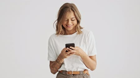 optimistický : Attractive young woman wearing a white basic t-shirt using her smartphone isolated over white background