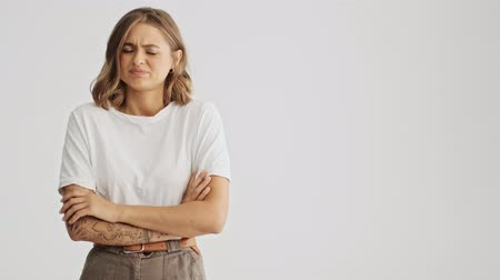 annoyance : Disappointment young woman wearing basic t-shirt standing with arms folded feeling distaste isolated over white background