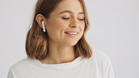 седые волосы : Pretty young woman wearing a white basic t-shirt starting listening to music on her wireless headphones isolated over white background