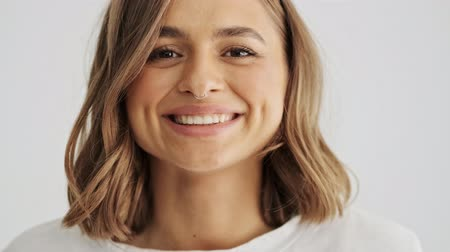 lekke band : Close up view of beautiful laughing young woman wearing basic t-shirt with nose piercing isolated over white background Stockvideo