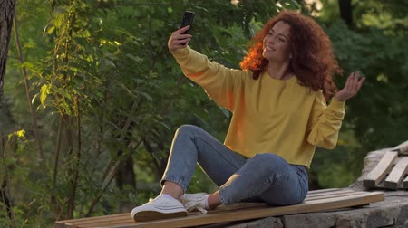 redhair : Glorious happy woman with curly redhead hair doing a hello gesture and sending an air kiss to her smartphone while sitting on bench in green park Stock Footage
