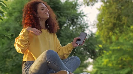 redhair : Cheerful young woman with curly redhead hair listening to music with smartphone and wired earphones while sitting on bench in green park Stock Footage