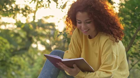 redhair : Positive young woman with curly redhead hair reading a book and drinking something hot in paper cup while sitting on bench in green park Stock Footage