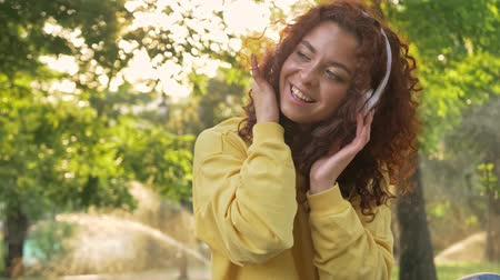 redhair : Attractive young woman with curly redhead hair listening to music with wireless headphones while sitting in green park