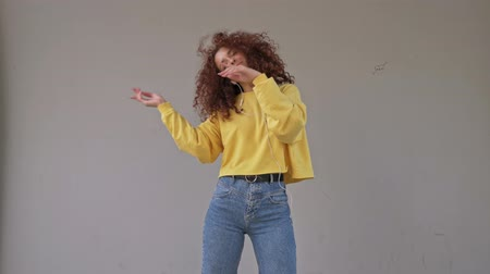 redhair : A cheerful young woman with curly redhead hair listening to music with wired headphones while dancing outside against a gray wall