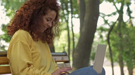 redhair : A pretty young attractive woman with curly redhead hair using her laptop while sitting on bench in green park
