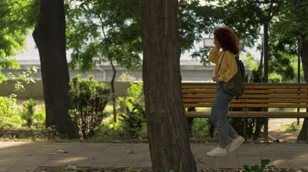 redhair : A cute young attractive woman with curly redhead hair wearing a yellow suit shot and jeans with backpack walking in green park Stock Footage