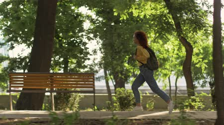 redhair : A nice young woman with curly redhead hair wearing a yellow suit shot and jeans with backpack running in green park Stock Footage