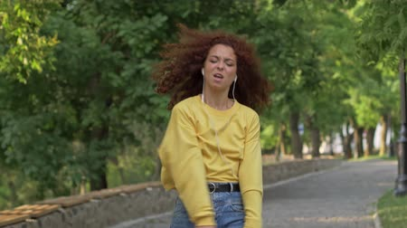 redhair : Happy young woman with curly redhead hair listening to music with wired headphones while dancing in green park Stock Footage