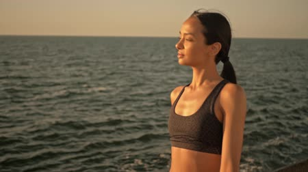 descanso : Positive young woman with lip piercing wearing black tracksuit going along the sea in the morning Stock Footage