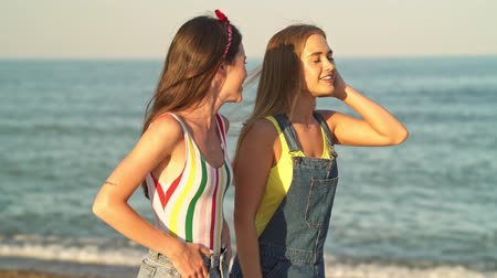 húszas évek : Pretty young girls are laughing while walking along the beach in summer
