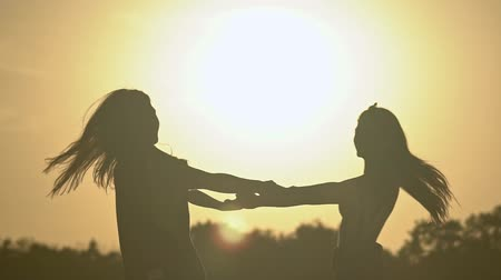 húszas évek : Silhouette of two young girls having fun at sunset in the summer