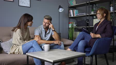 psychotherapist : Serious couple man and woman having a conversation with a psychologist on therapy session in the room