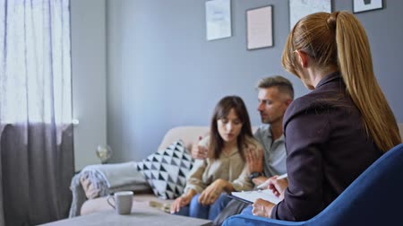 puzzled : Puzzled caucasian couple man and woman having conversation with psychologist on therapy session in room Stock Footage